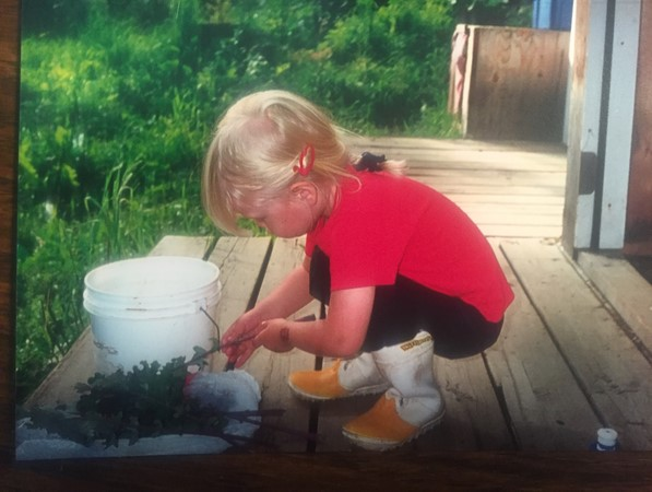 My daughter cleaning the kale she grew in her garden patch